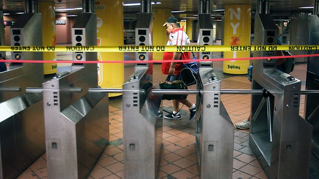 Turnstiles are barricaded with caution tape shortly before the New York City Subway system suspended service for the first time ever, as preparations are made for Hurricane Irene, in New York. Picture: Mike Groll / AP