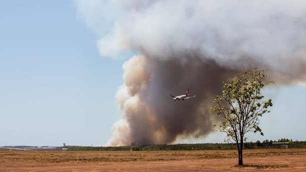 A plane landing at Darwin Airport earlier today, with smoke from the large grass fire burning nearby. Picture: Emma Munday