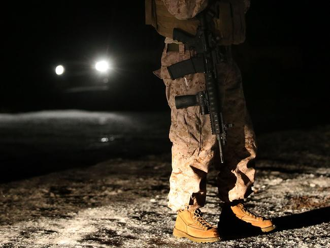 A member of an anti-government militia holds an assault rifle as he stands guard at a checkpoint in front of the Malheur National Wildlife Refuge Headquarters.