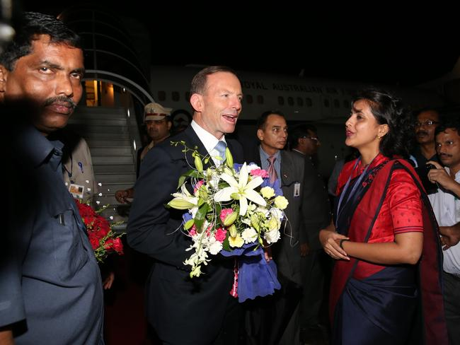 Tony Abbott is presented with flowers as he arrives in Mumbai.