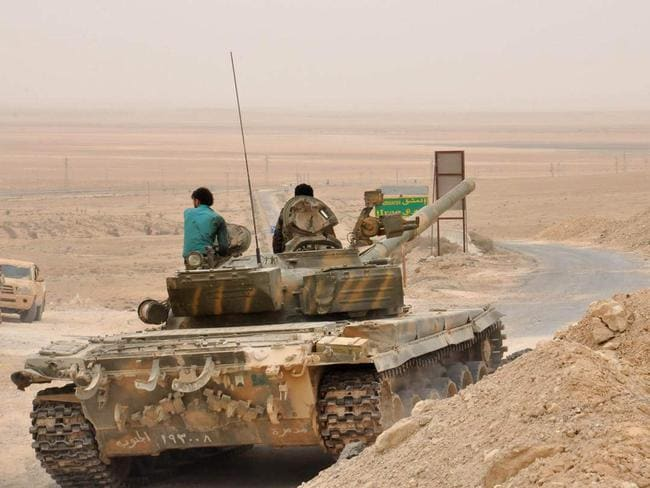 In this photo released by the Syrian official news agency SANA, Syrian soldiers sit on top of a tank during fighting in Palmyra, Syria. Picture: SANA via AP