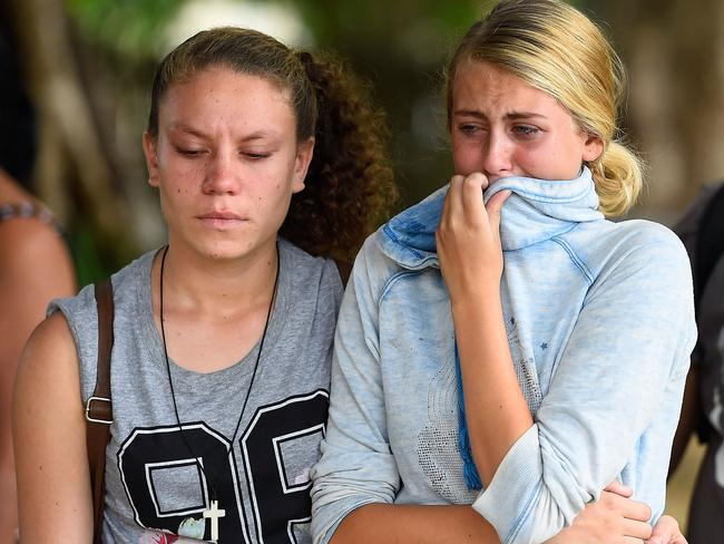 Distraught locals weep near the scene of the mass murder.