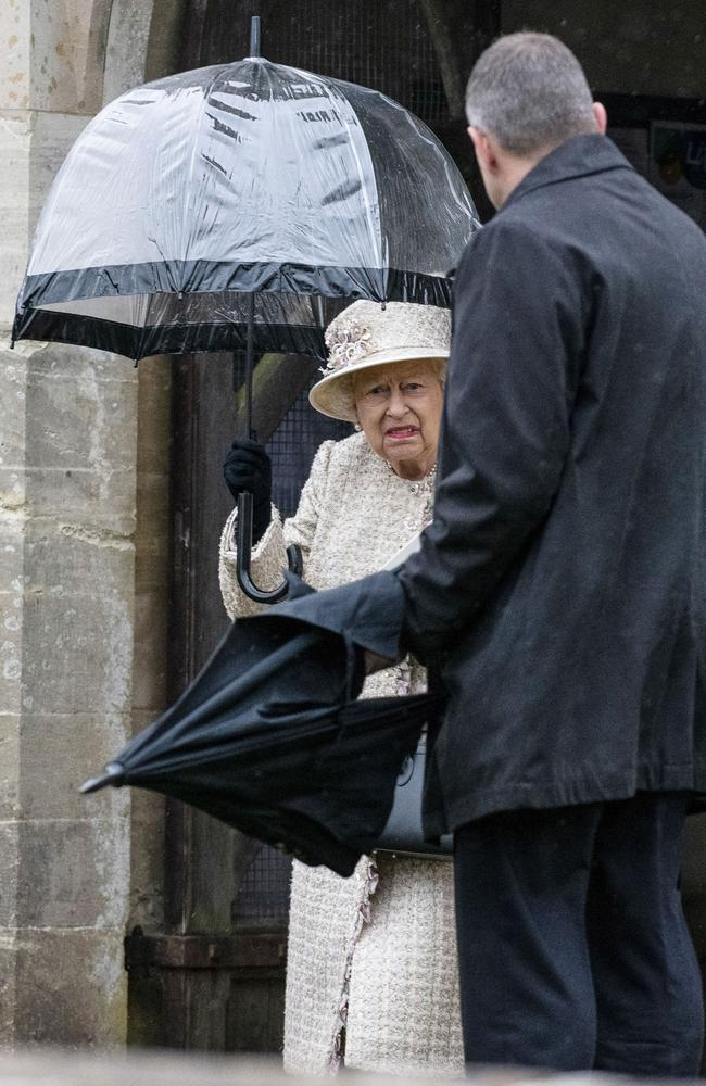 The Queen holds her own brolly — and looks less than thrilled about it. Picture: Andrew Lloyd / SplashNews.com