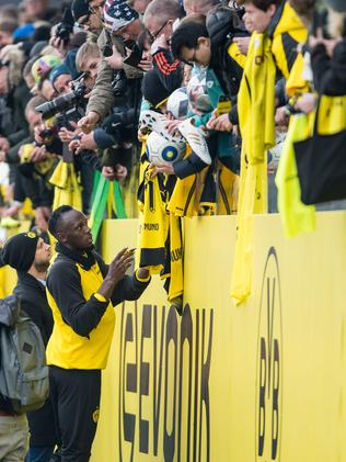Retired Jamaican Olympic and World champion sprinter Usain Bolt signs autographs