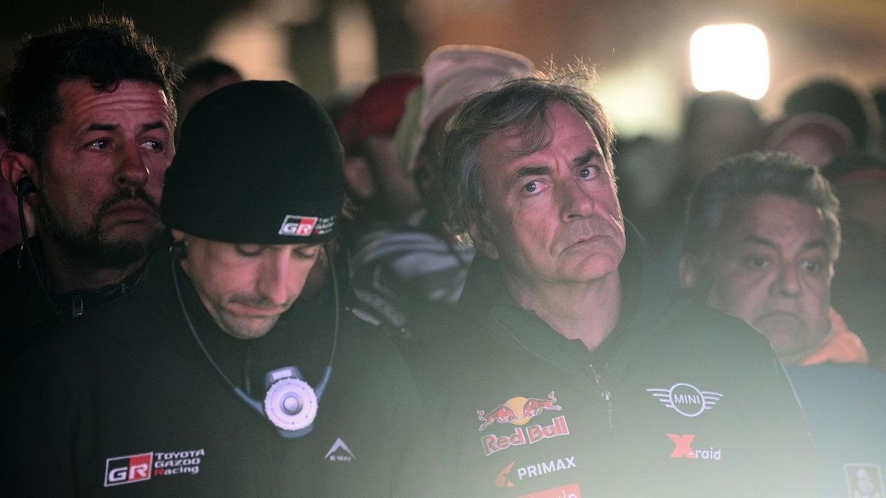 Current cars leader Carlos Sainz (R) at the minute's silence. (Photo by FRANCK FIFE / AFP)