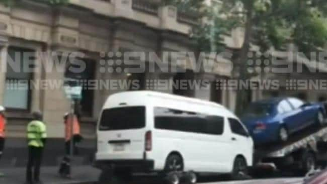 Workers unwrap the sign before the van is towed away. Picture: Channel 9