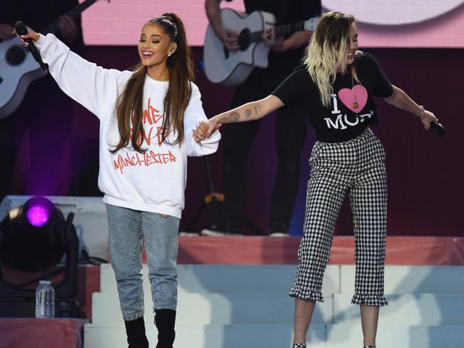 Ariana, pictured here with Miley Cyrus, was at times overcome with emotion during the show. Picture: Getty Images/Dave Hogan for One Love Manchester