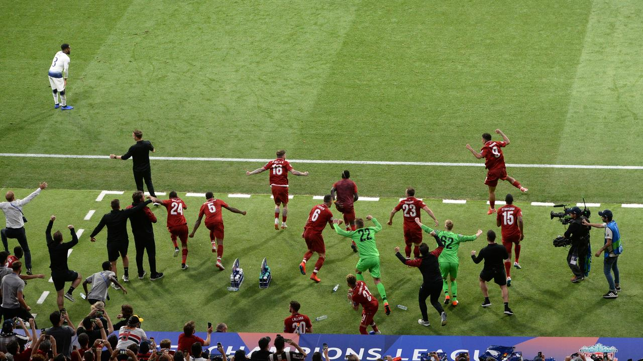 Liverpool players and staff celebrate victory at full-time