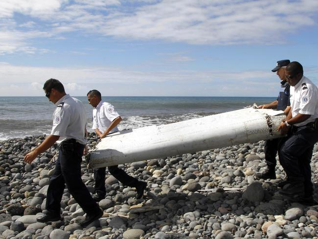 A file photo dated 29 July 2015 showing officers carrying a flaperon from an aircraft apparently washed ashore in Saint-Andre de la Reunion, eastern La Reunion island, France. Picture: EPA