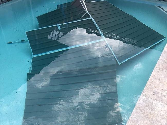 A mangled shed is pictured submerged in a suburban Sydney backyard pool.