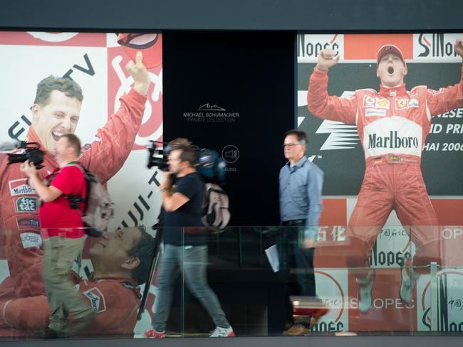 Journalists pass by photographs of former German Formula one driver Michael Schumacher during a press presentation of Schumacher´s Private Collection. Picture: AFP