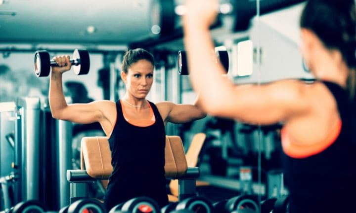 Young woman doing shoulder exercise in the gym with dumbbell