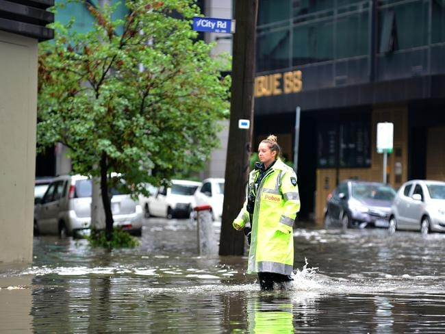 A police officer up to her ankles in floodwaters at Melbourne's Southbank. Picture : Nicki Connolly