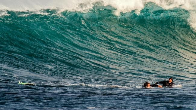 A surfer helps a fellow board rider, left, who had just been attacked by a shark in Gracetown, WA. Picture: Peter Jovic for The Australian