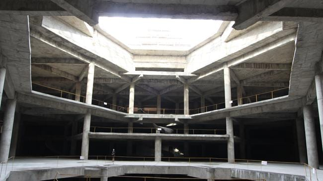 A visitor stands on the ground floor of the unfinished hotel in 2012. Picture: AP