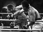 Perspiration flies from the head of defending heavyweight champion boxer George Foreman as he takes a right from challenger Muhammad Ali during their world heavyweight championship bout dubbed 'Rumble in the Jungle' in Kinshasa, Zaire, 30/10/1974. Picture: Ed Kolenovsky / Associated Press