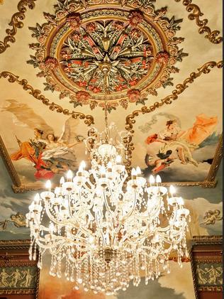 A chandelier below Michelangelo-inspired, handpainted ceilings.