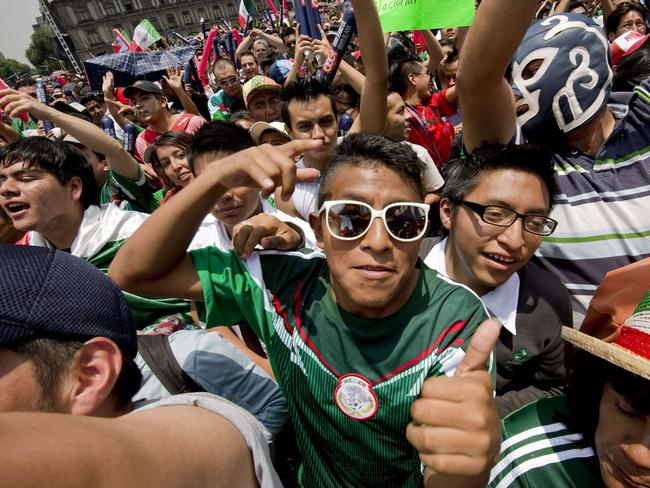 Mexican fans react during the broadcasting of the Mexico vs Brazil FIFA World Cup football match, at Zocalo Square in Mexico City.