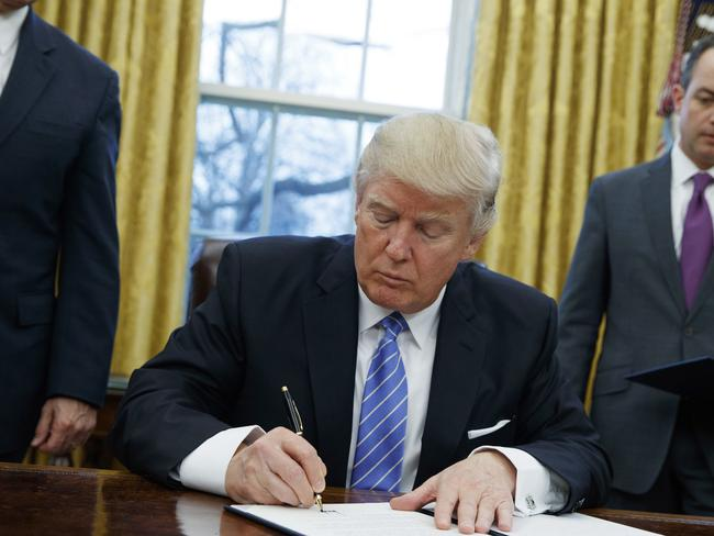 President Donald Trump signs an executive order to withdraw the US from the 12-nation trans-Pacific Partnership trade pact. Picture:Evan Vucci.