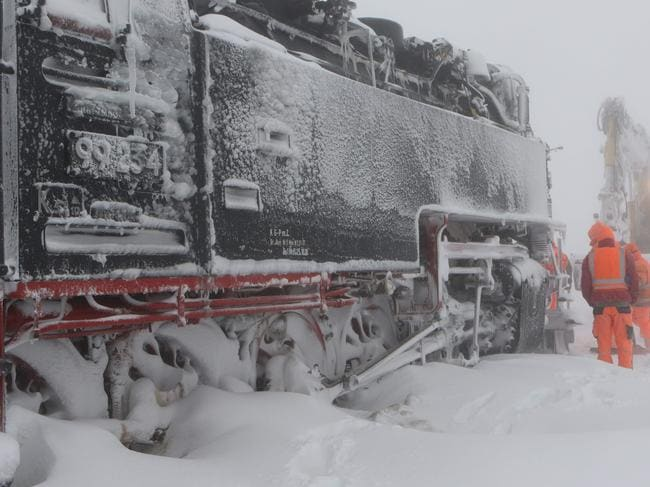 Workers try to free a train that got stuck in the snow on Brocken mountain in the Harz region in central Germany after a snow blizzard. Picture: AFP