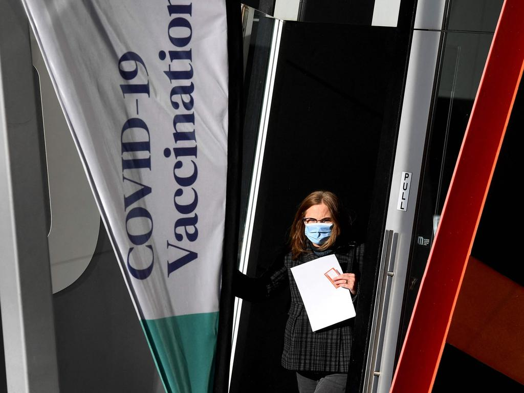 A woman emerges from a Covid-19 vaccination centre in Melbourne on May 24, 2021 as the city records four new locally acquired cases of Covid-19 in the community after 85 day free of the virus. (Photo by William WEST / AFP)