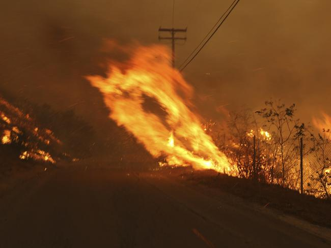 Wind-driven flames from a wildfire race up a slope and cross the road in Malibu. Picture: AP