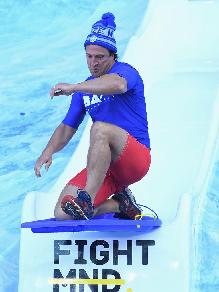 Bulldogs head coach Luke Beveridge goes down the Freeze MND slide. (Photo by Quinn Rooney/Getty Images)