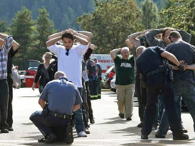 Police search ... officers frisk students outside Umpqua Community College in Roseburg, Oregon. Picture: Mike Sullivan/Roseburg News-Review via AP