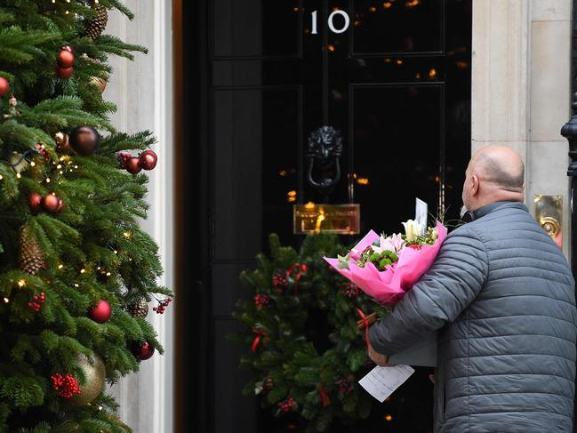 A man delivers flowers addressed to Britain's Prime Minister Theresa May, at 10 Downing Street in central London. Picture: AFP