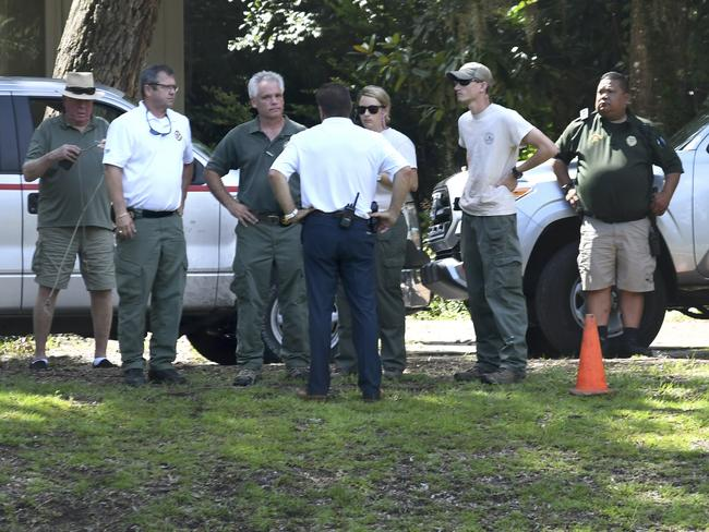 Law enforcement stand near where authorities say Cassandra Cline was dragged into a lagoon by an alligator and killed. Picture: Drew Martin/The Island Packet