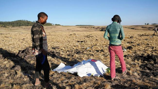 Local residents look at debris at the scene where Ethiopian Airlines Flight 302 crashed in a wheat field just outside the town of Bishoftu. Picture: Jemal Countess/Getty Images.