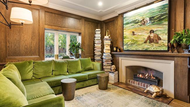 Wood panelling and an open fireplace give the space a cosy ambience.