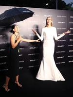 American model Karlie Kloss reacts as she stands in heavy rain on the red carpet as she arrives to the David Jones Autumn Winter 2017 collections launch in Sydney, Wednesday, Feb. 1, 2017. (AAP Image/David Moir)