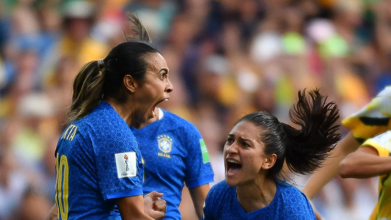 Brazil's forward Marta (L) celebrates with teammates after scoring a penalty