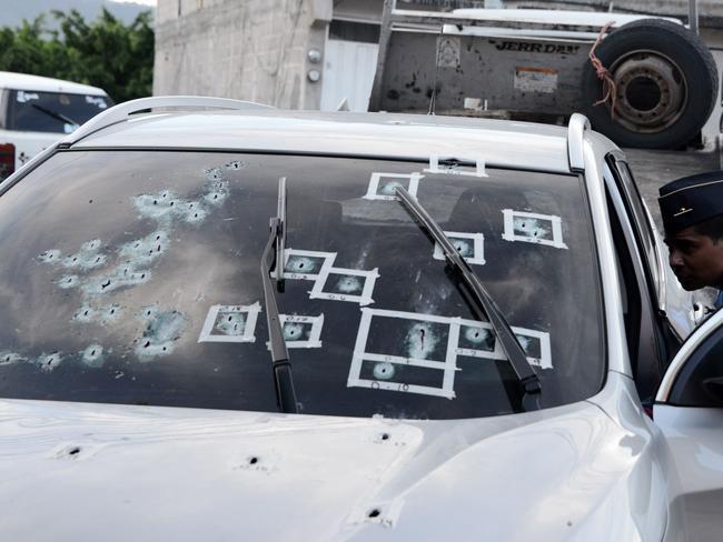 Honduran policemen inspect a car peppered by bullets in Tegucigalpa, Honduras, last week. Orlando Sierra/AFP