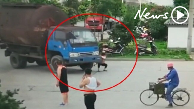 Moment woman attempts to scam driver by lying in front of truck