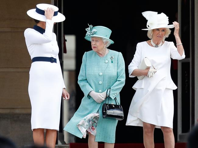US First Lady Melania Trump (L) and Britain's Camilla, Duchess of Cornwall (R) hold their hats before they are caught by the wind as Britain's Queen Elizabeth II (C) stands with them during a welcome ceremony at Buckingham Palace. Picture: Adrian DENNIS / AFP.