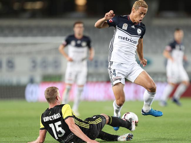 Keisuke Honda of the Victory is tackled by Michal Kopczynski of the Phoenix. Picture: AAP Image/David Rowland