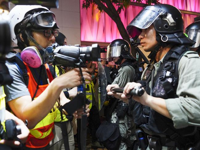Riot police stop members of the media as they detain protesters in Hong Kong. Picture: AP