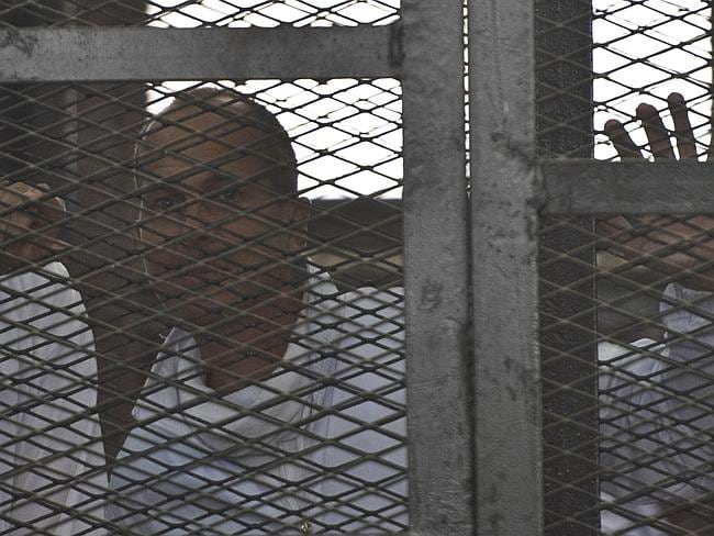 Wave goodbye ... Australian journalist Peter Greste of Al-Jazeera looks leaves the defendants cage after his hearing at Cairo's Tora prison. Picture: AFP / KHALED DESOUKI
