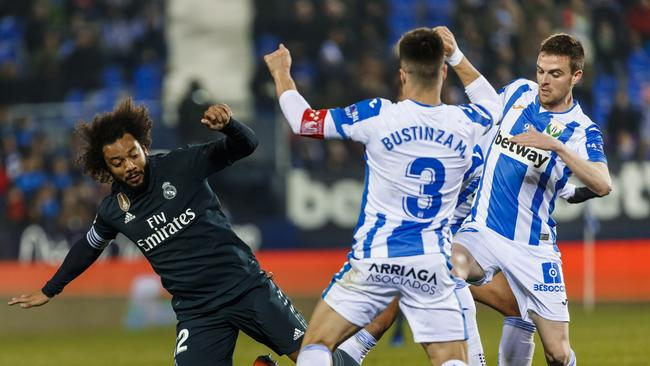 Real Madrid's Marcelo, left, duels for the ball with Leganes' Unai Bustinza