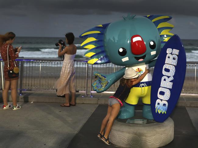 A girl hugs Commonwealth Games mascot, Borobi, at the Surfers Paradise. Picture: AP