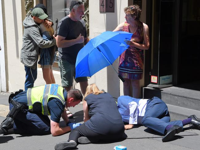 Bystanders comfort each other after pedestrians were mowed down. Picture: Tony Gough