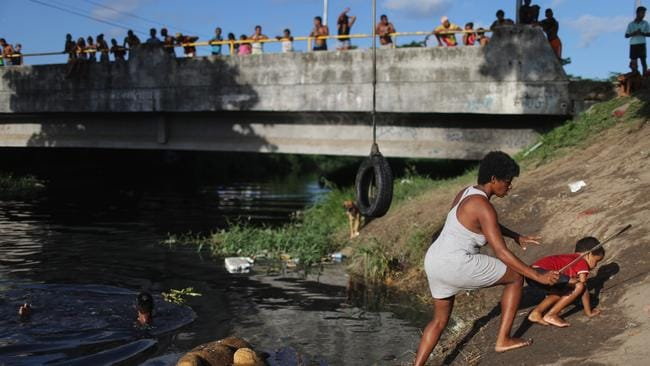 People gather and swim along a polluted and slow-moving canal on in Recife, Pernambuco state, Brazil. Stagnant water is a potential breeding sites for mosquitos that carry the Zika virus. Picture: Mario Tama / Getty Images