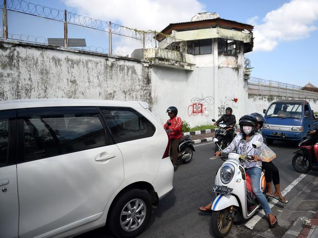 Motorcyclists ride their vehicles past the Kerobokan prison in Denpasar on Indonesia's resort island of Bali. Four foreign prisoners tunnelled out of the jail, including an Australian. Picture: AFP / SONNY TUMBELAKA