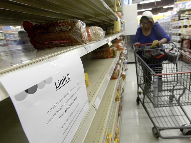 A woman pushes her cart next to a nearly empty shelf of bread in a grocery store in Port Arthur, Texas. Picture: AP