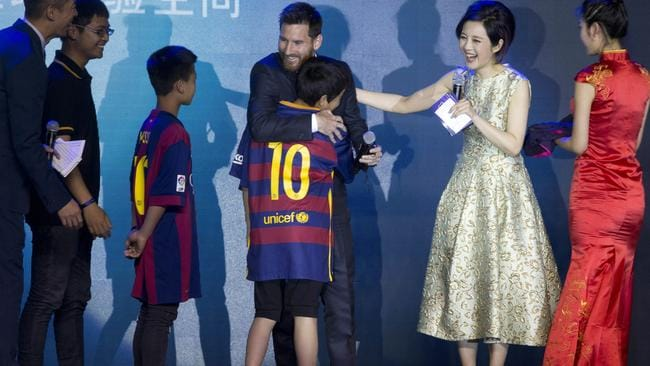 Messi, centre, hugs young footballers.