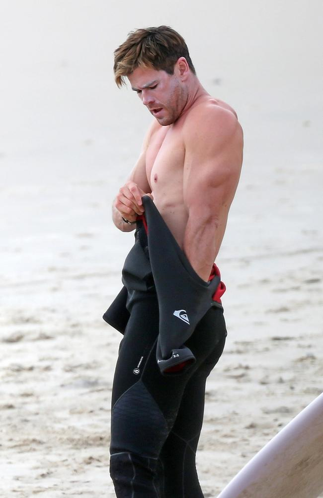 Hemsworth even looks good with zinc all over his face trying to get into a wetsuit. That is no mean feat. Pictures: Backgrid