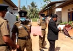 Sri Lankan magistrate Wasantha Ramanayake (right) and police officers at the house where the girl died during an exorcism on February 28, 2021.