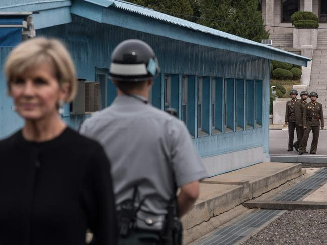 North Korean soldiers (rear) watch as Australia's Foreign Minister Julie Bishop (L) stands on the southern side of the military demarcation line between North and South Korea at the truce village of Panmunjom. Picture: AFP